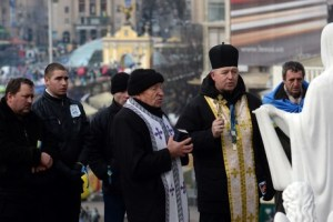 Priests and faithful of the Ukrainian Greek Catholic Church pray in front of a statue of the Mother of God at the Independence Square in Kiev on December 4, 2013, as part of protest over the government's turn-back on a deal with the European Union. AFP PHOTO/ VASILY MAXIMOV
