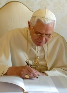 Pope Benedict signing Caritas in Veritate.