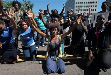 Protesters dropped to their knees and put their arms in the air during a rally Tuesday for Michael Brown, who was shot and killed by a Ferguson, Mo., police officer. Laurie Skrivan The Associated Press