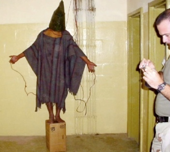 A soldier checks a digital camera while an Abu Ghraib prisoner stands connected to a battery.
