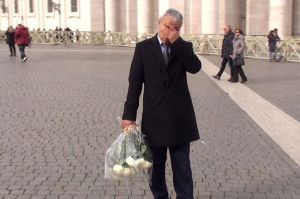 Over 30 years later, Mehmet Ali Agca stands in St. Peter's Square before placing the white roses on John Paul II's tomb.