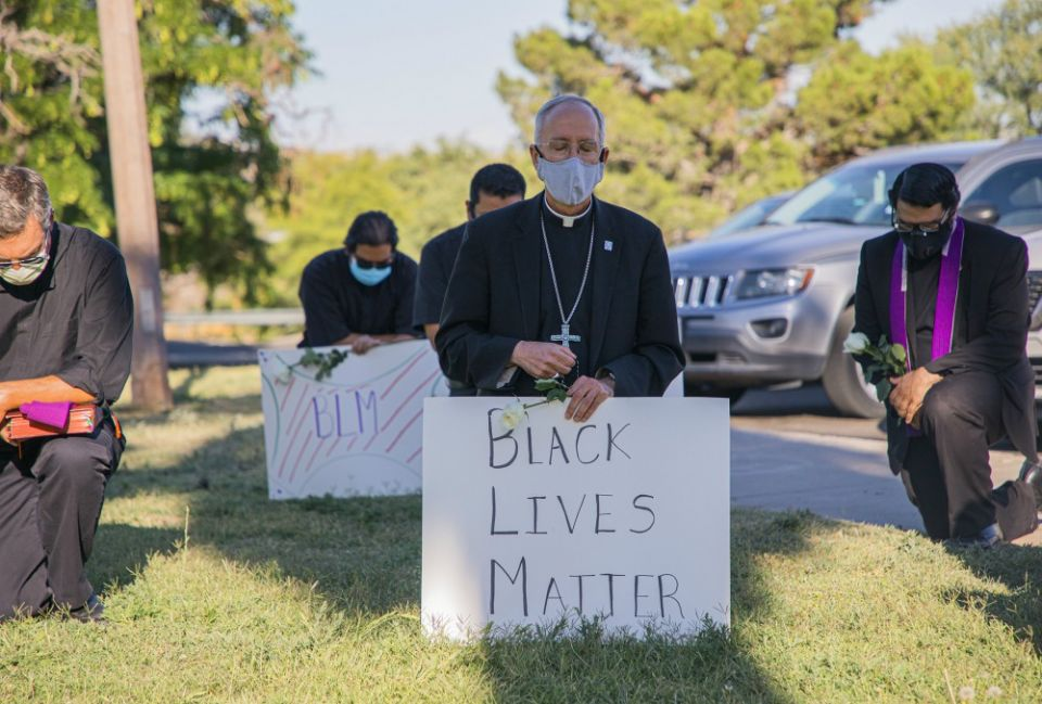 Bishop Mark Seitz of El Paso, Texas, kneels at El Paso's Memorial Park holding a Black Lives Matter sign June 1. Seitz and other clergy from the diocese prayed and kneeled for eight minutes, the time George Floyd, an unarmed black man, spent under a police officer's knee before dying May 25. (CNS/Courtesy of El Paso Diocese/Fernie Ceniceros)
