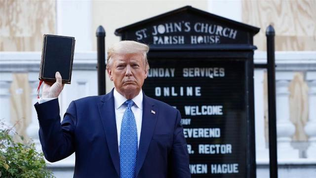 Donald Trump holds a Bible as he visits outside St John's Church across Lafayette Park from the White House on Monday, June 1, 2020, in Washington, DC. Part of the church was set on fire during protests on Sunday night [Patrick Semansky/AP Photo]