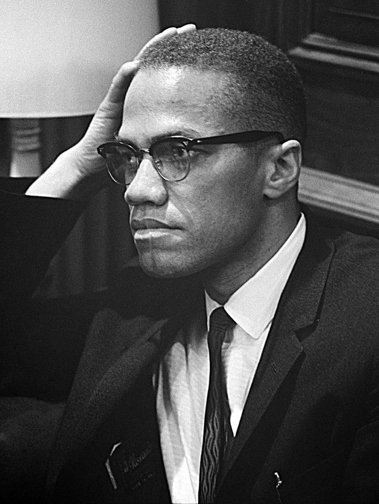 Malcolm X waiting for a press conference to begin on March 26, 1964. Public domain.